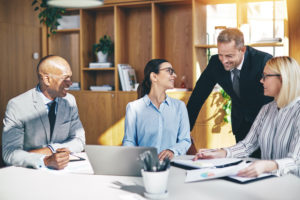 Diverse businesspeople laughing together during an office meeting